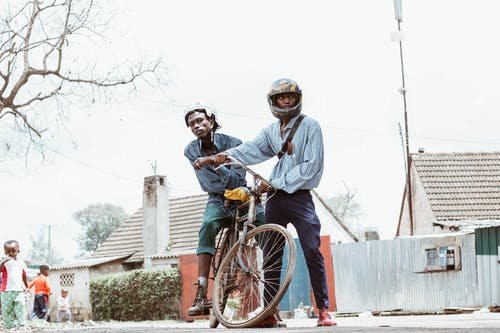 Person Wearing Helmet Holding Bicycle With Man Riding