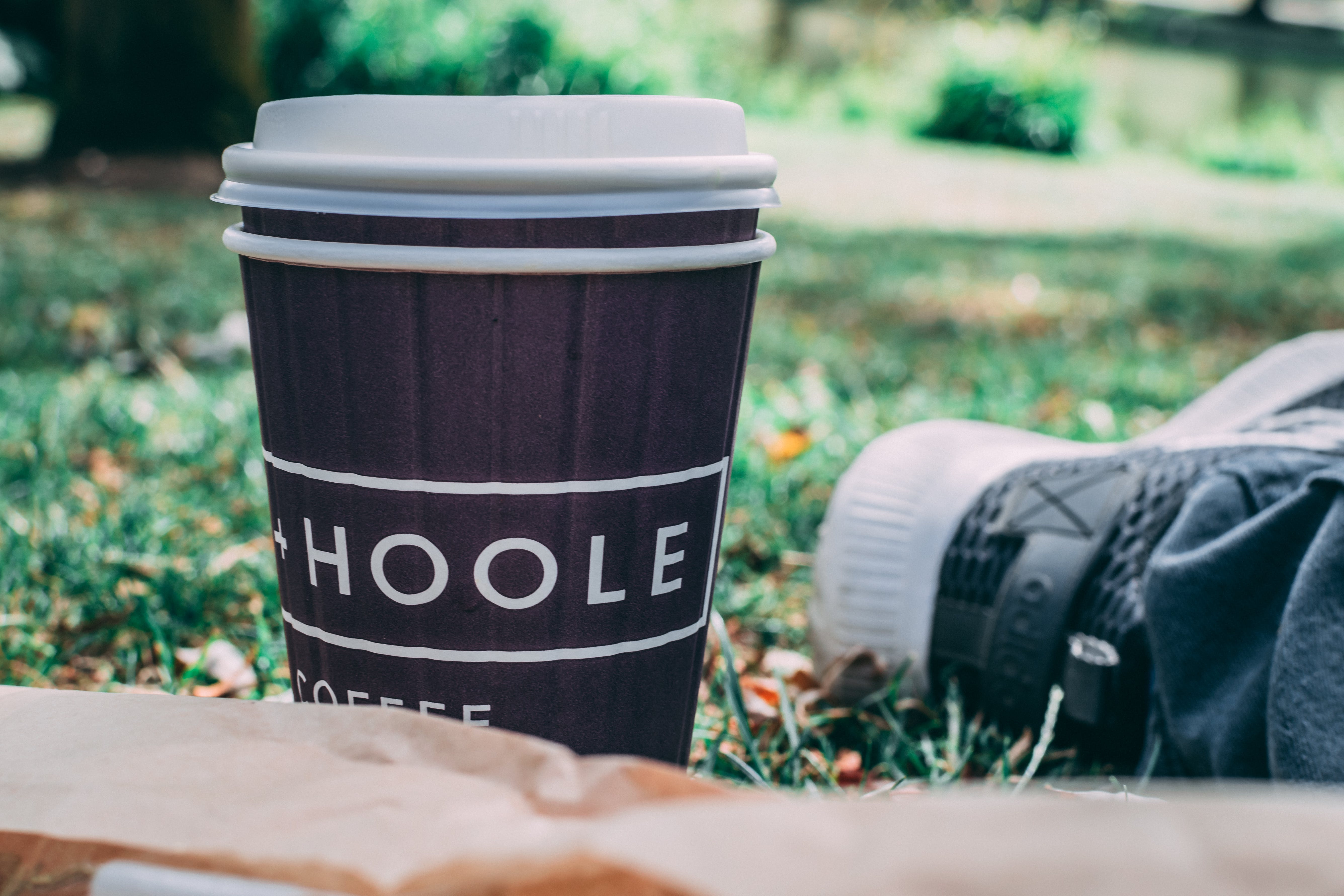 Black and White Coffee Cup on Green Grass