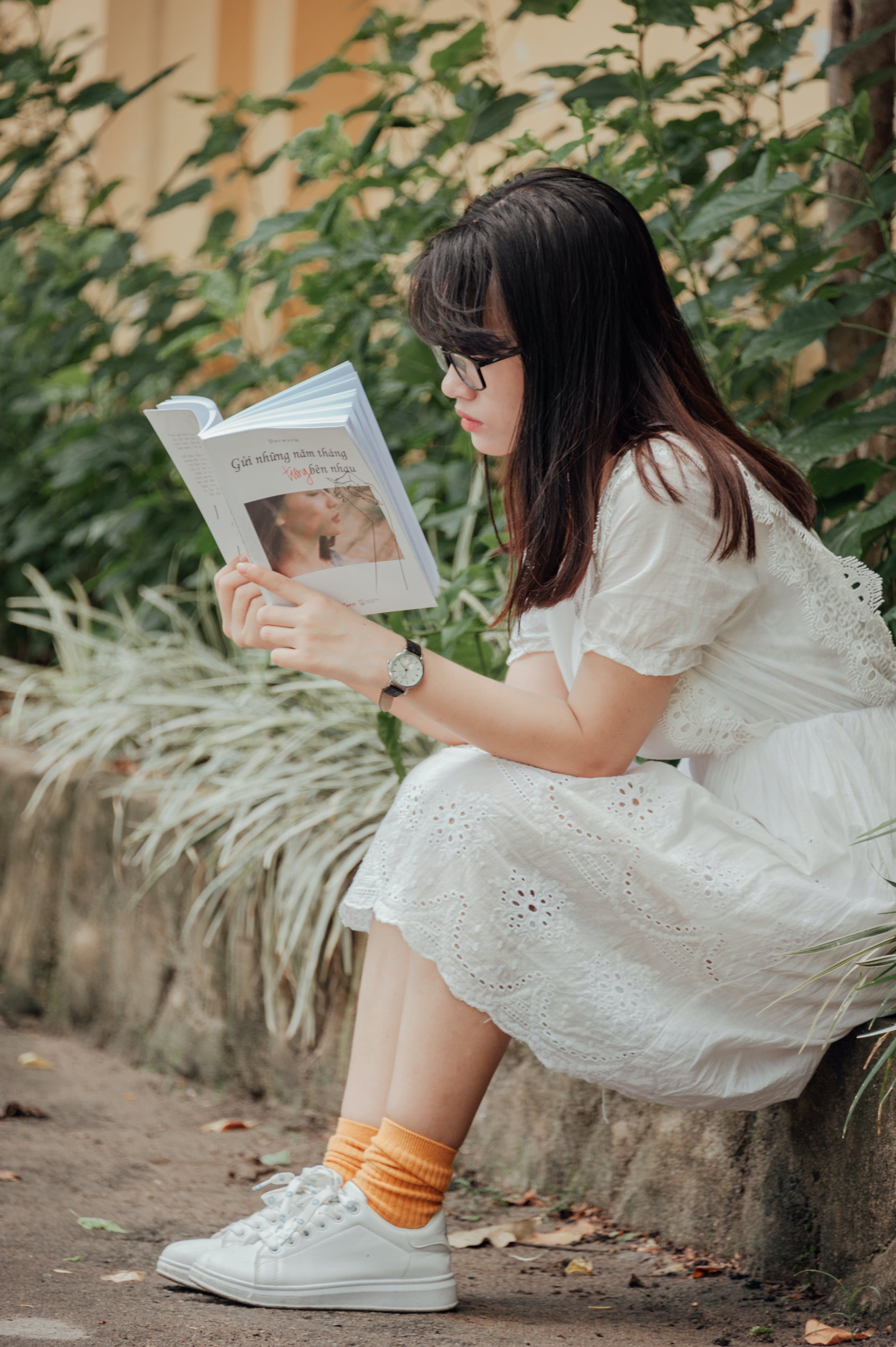 Woman Sitting on Gray Concrete Block Reading Book