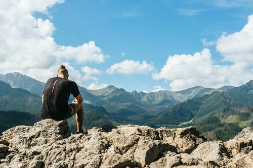 Man Sitting on Rocks Within Mountain Range