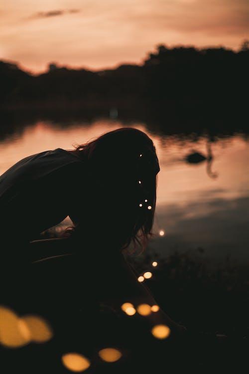 Silhouette De Femme Près Du Plan D'eau Pendant L'heure D'or