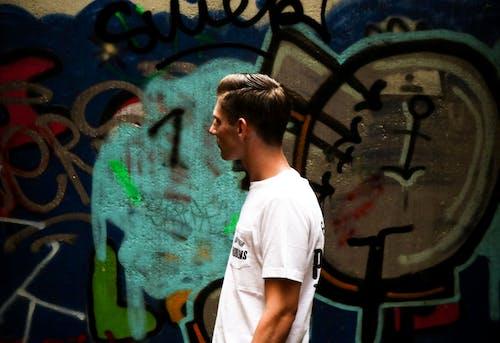 Man Facing Sideways Looking at Wall Painting