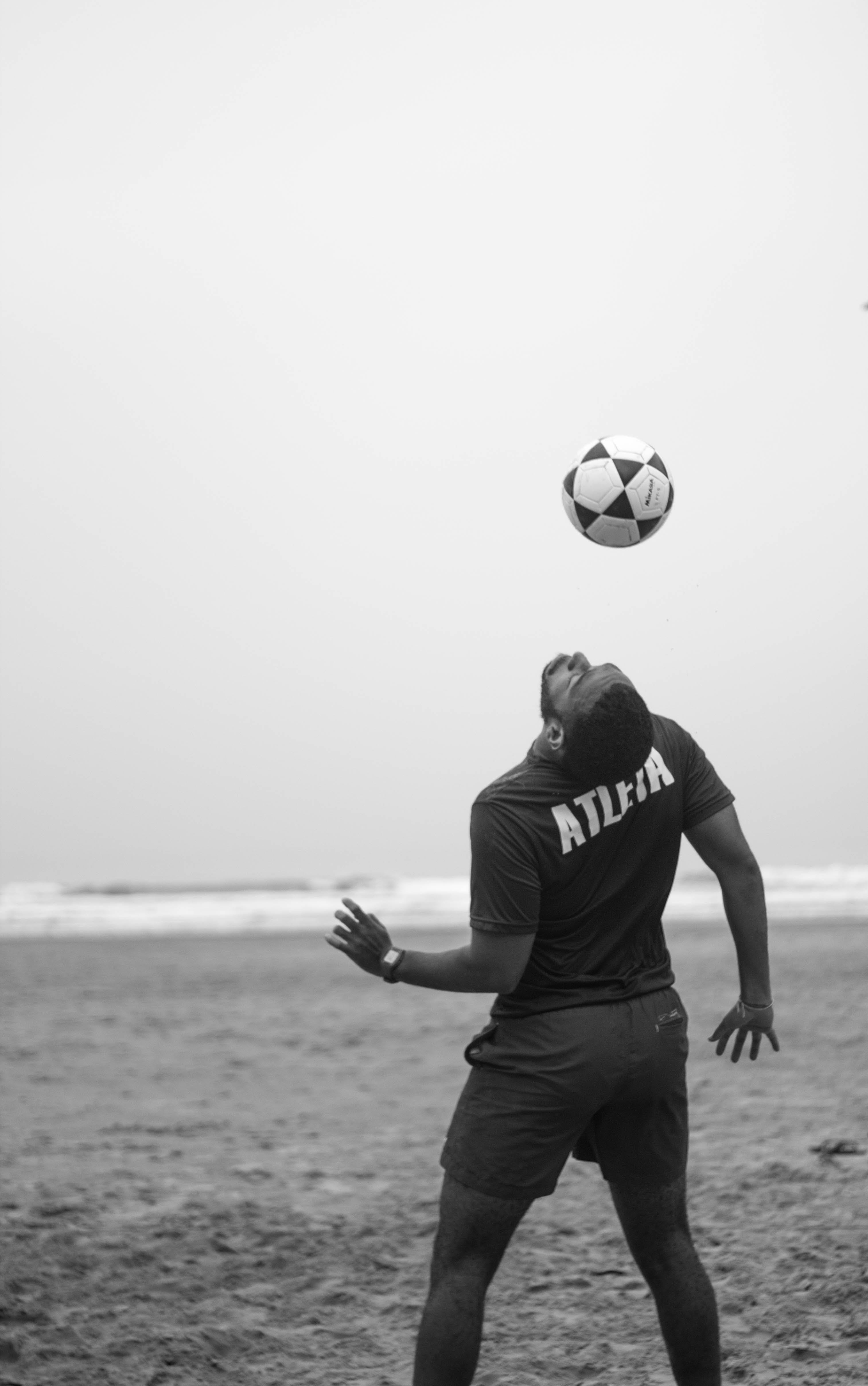 Man on Shore Doing Soccer Trick
