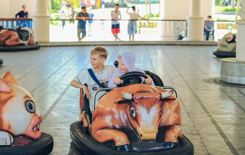 Two Boys Riding on Orange and Black Bumper Car