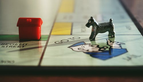 Dog and House Toy on Monopoly Board Game