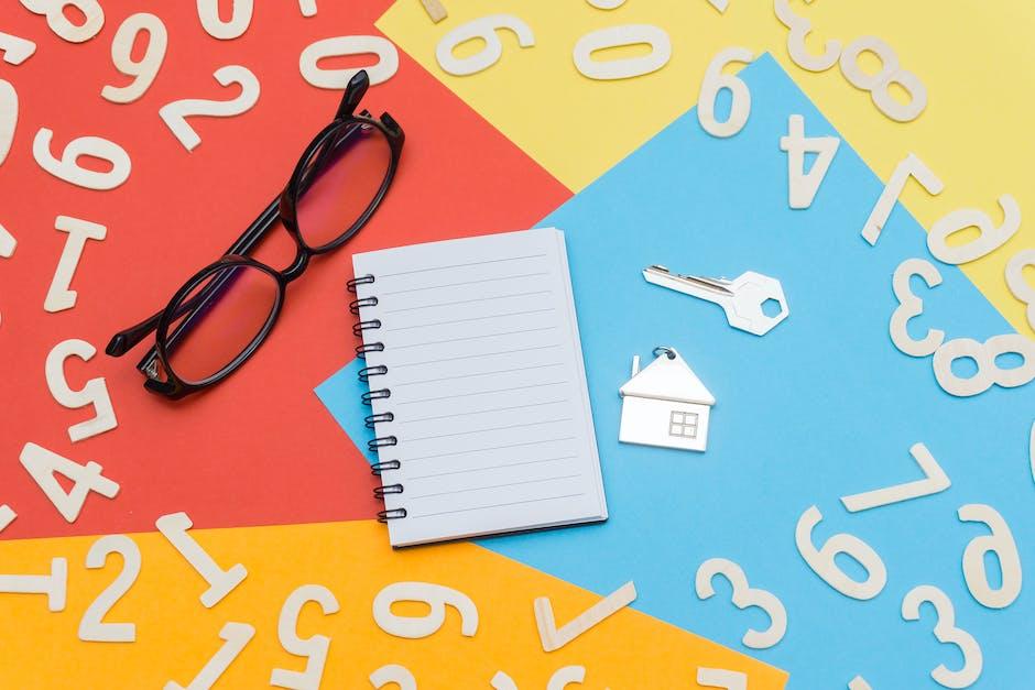 Eyeglasses near notebook and metal key