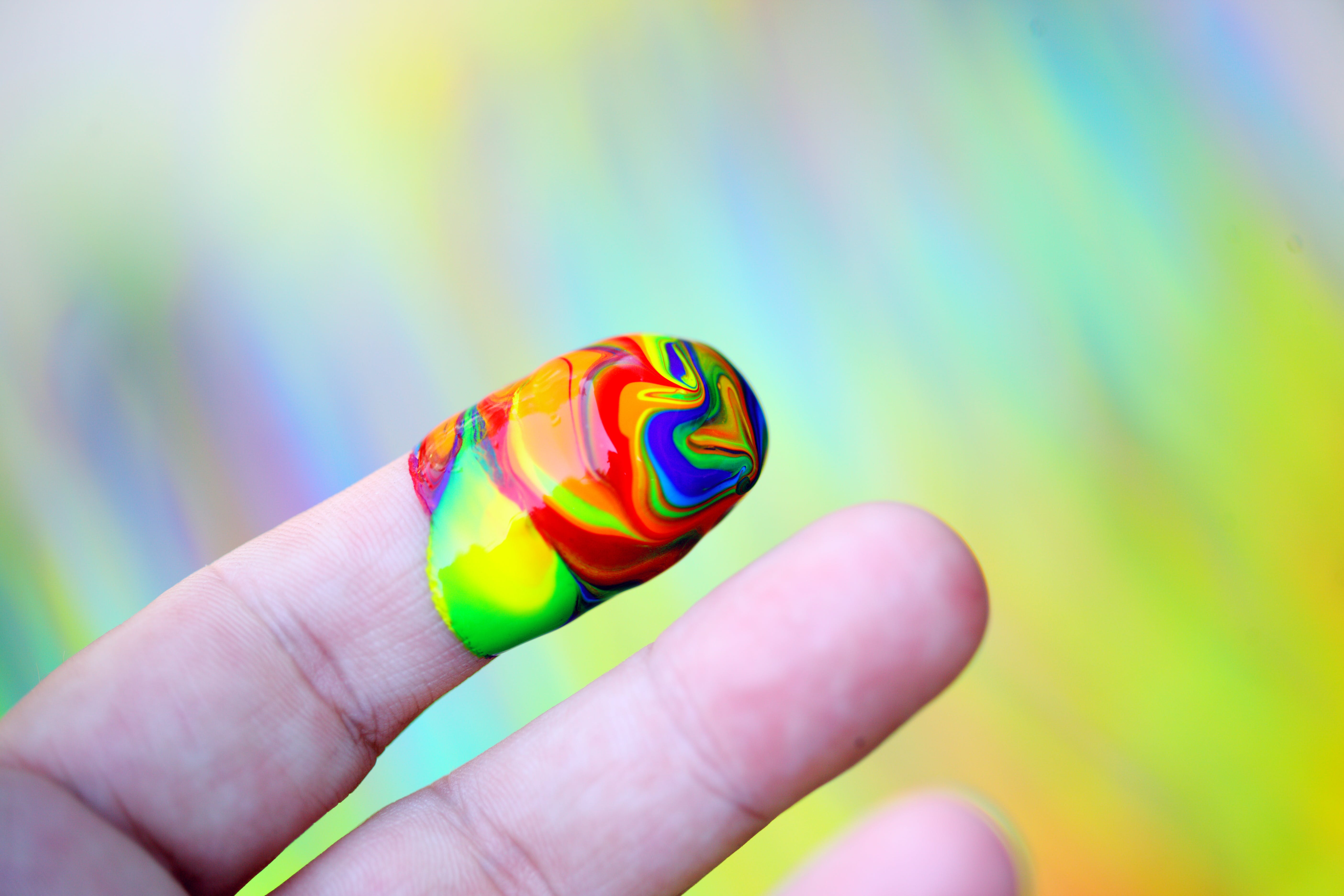 Person Showing Multi-coloured Paint On His Index Finger