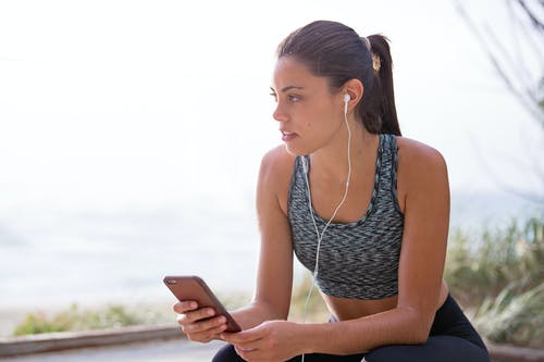 Woman Holding Smartphone While Sitting