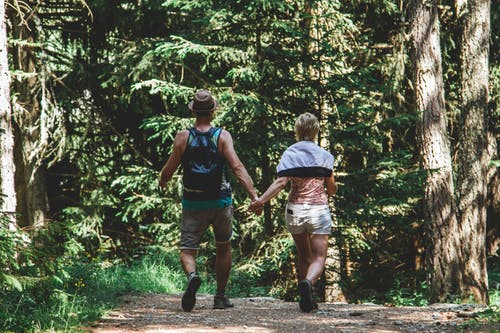 Man and Woman Walking in Forest