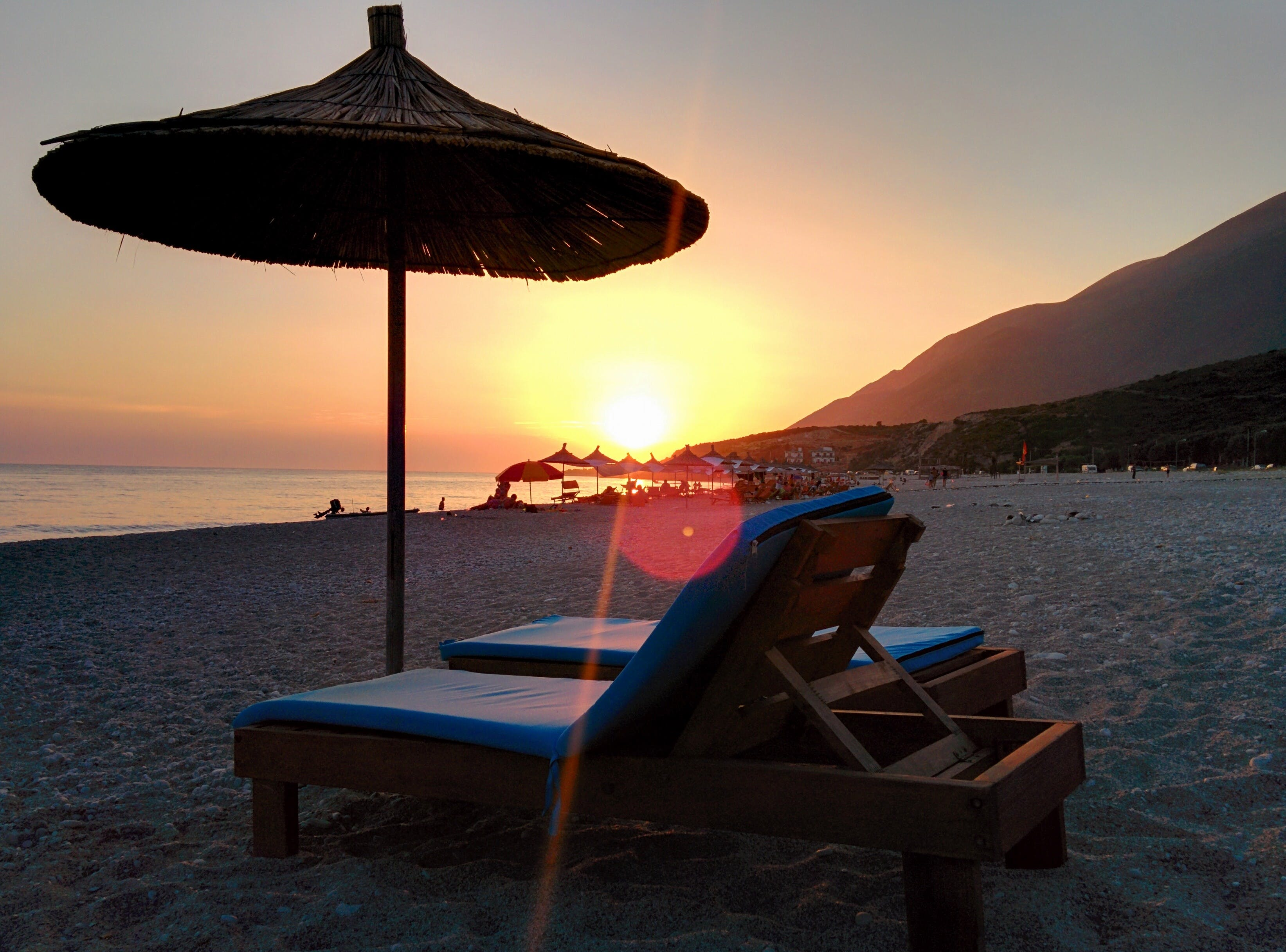 Brown Wooden Lounger on Seashore during Day Time