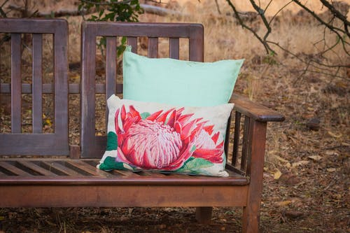 White Pillow With Lotus-printed on Brown Wooden Bench at the Park