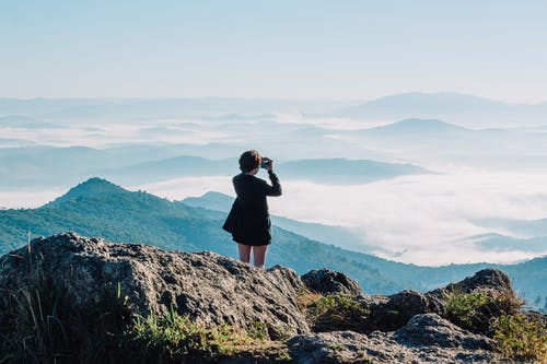 Woman Taking A Picture Of Mountains