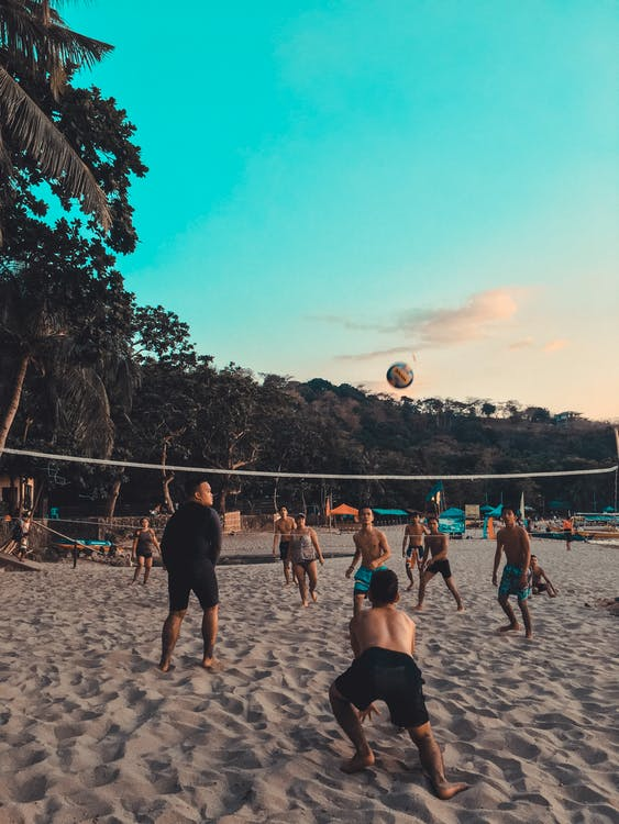 Group of People Playing Beach Volleyball on Shore