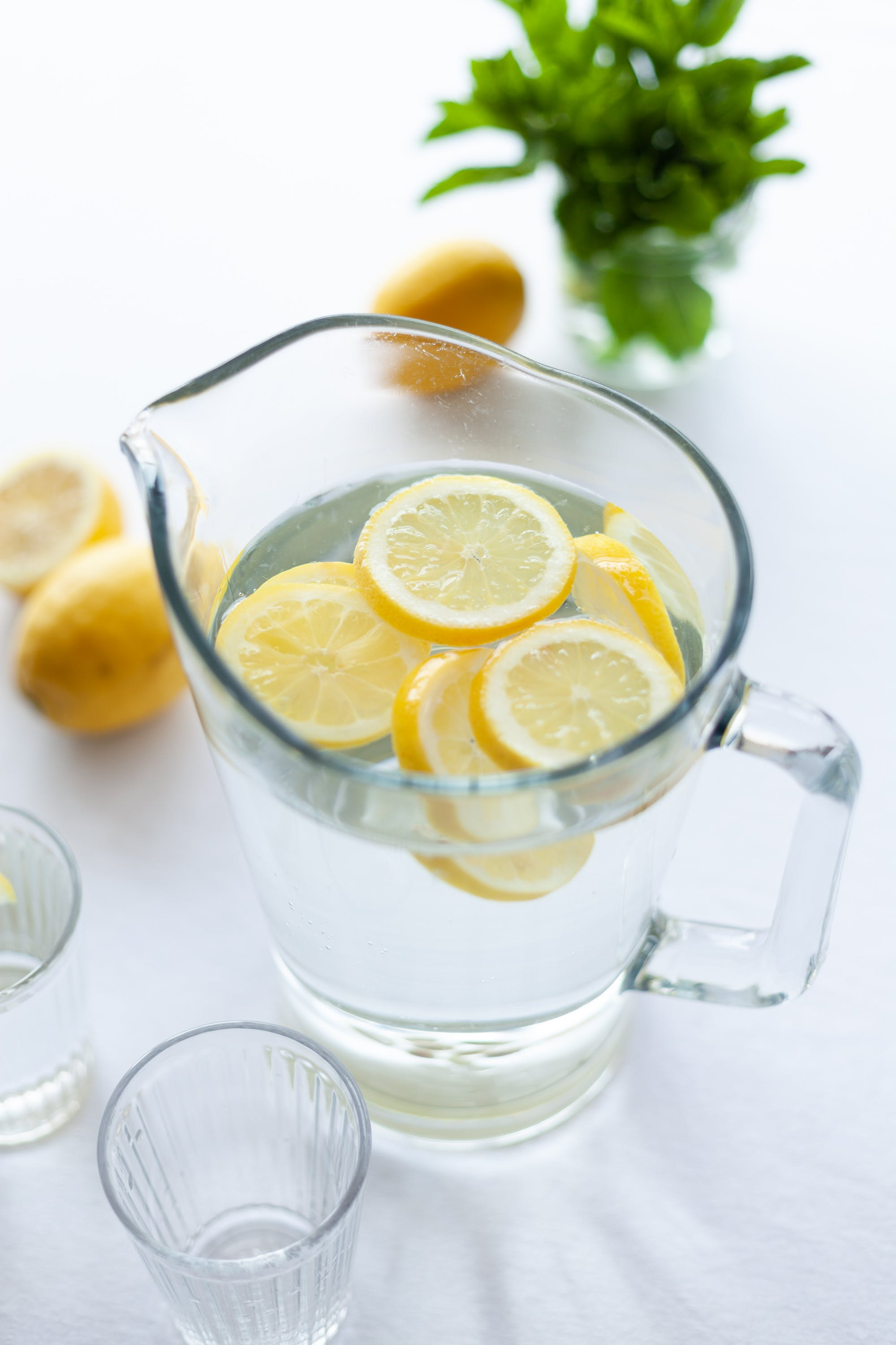 Clear Glass Pitcher Filled With Clear Liquid and Slices of Lemon
