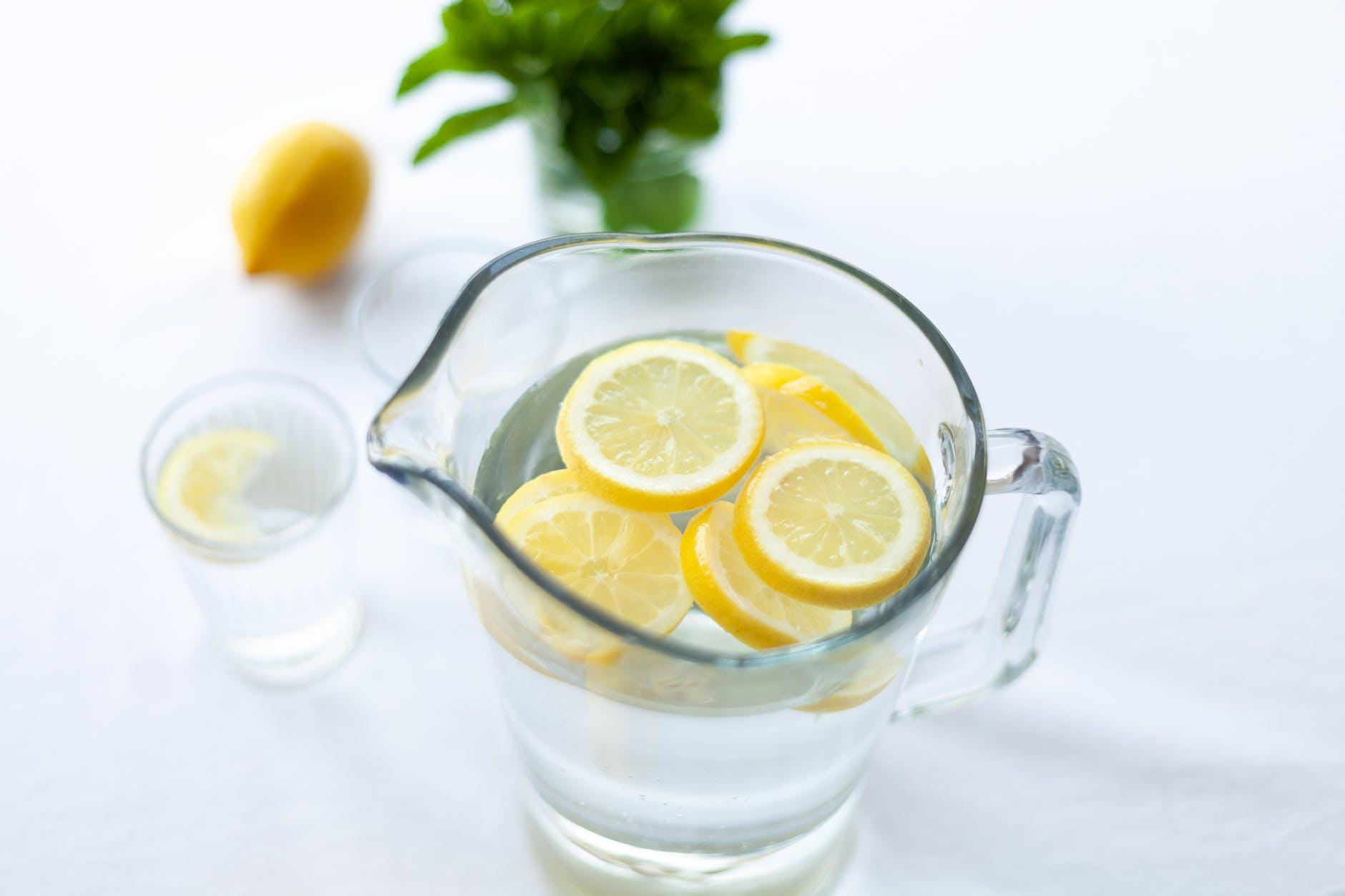 Sliced lemon fruit in glass pitcher