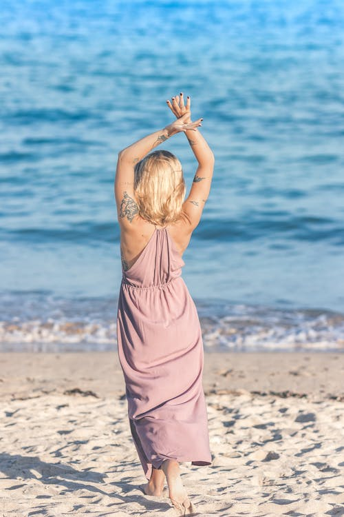 Woman Facing Body of Water Raising Her Hands Up