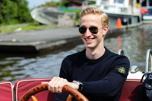 Smiling Man Driving Motorboat on Body of Water