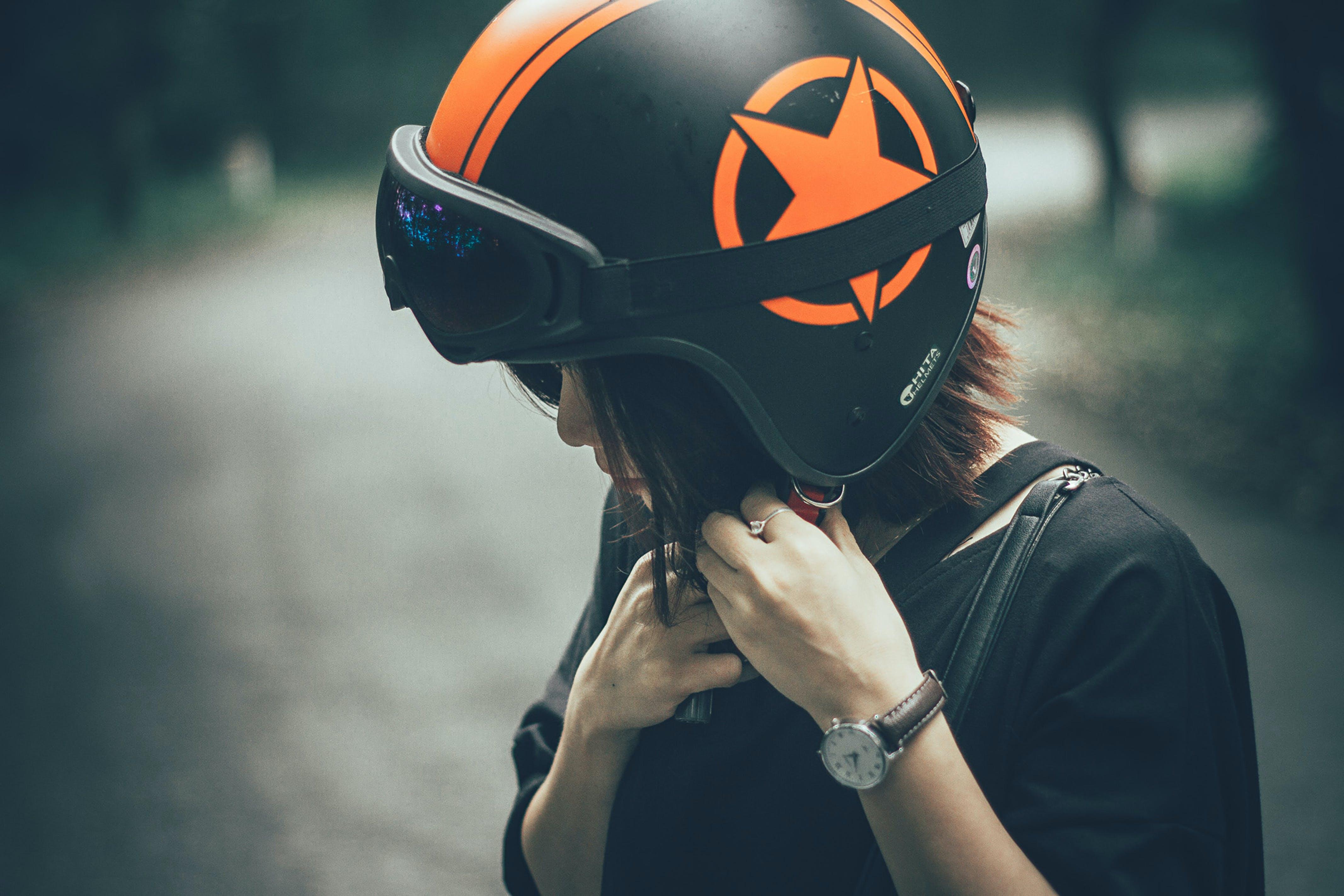 Woman on Black and Orange Half-face Helmet