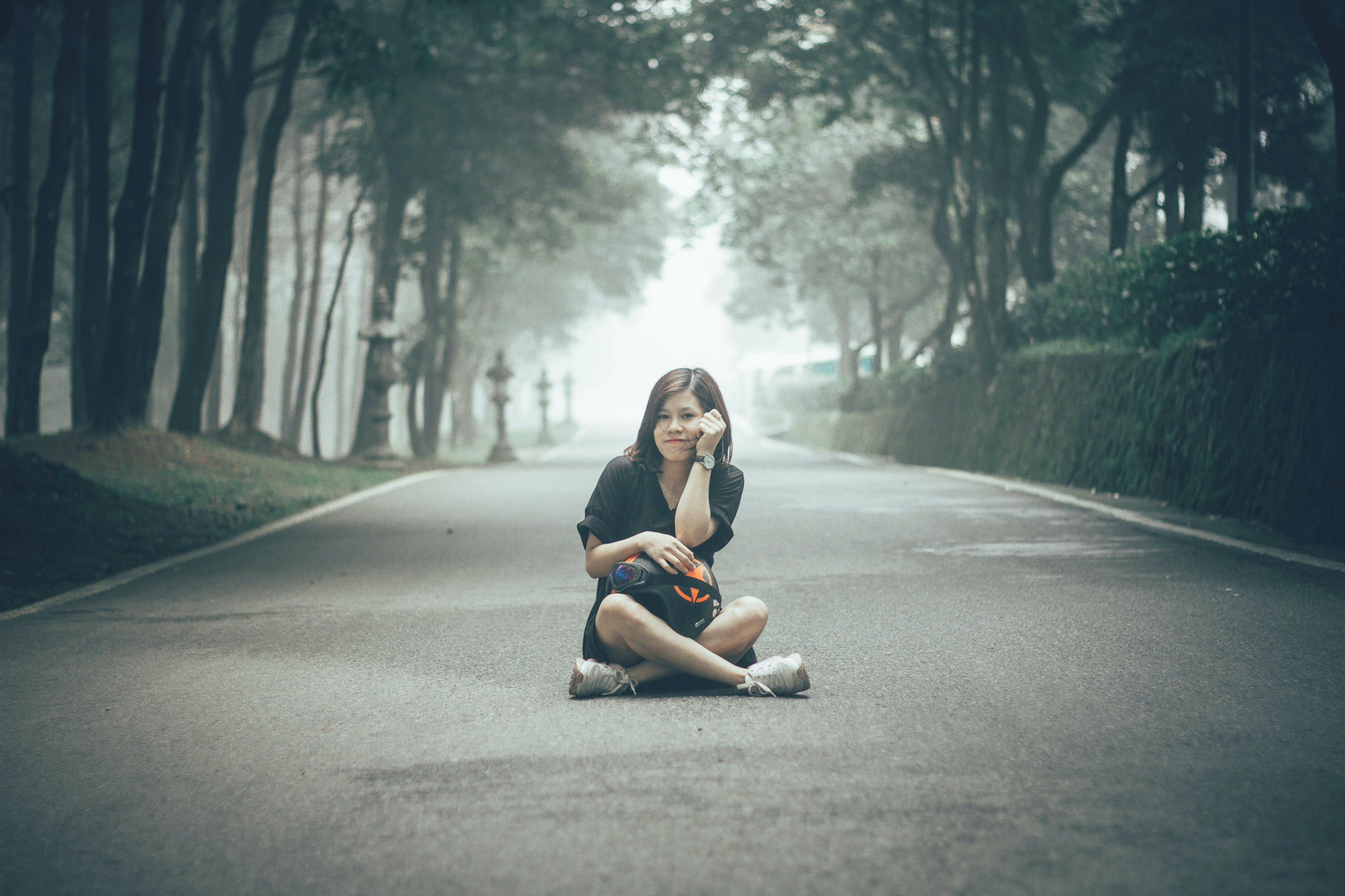Girl Sitting on Gray Concrete Road