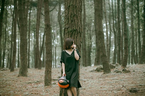 Woman in Black V-neck Elbow-sleeved Midi Dress Near Trees Holding Half-face Helmet
