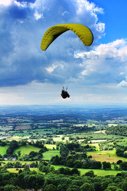 Person Paragliding Under Cloudy Sky