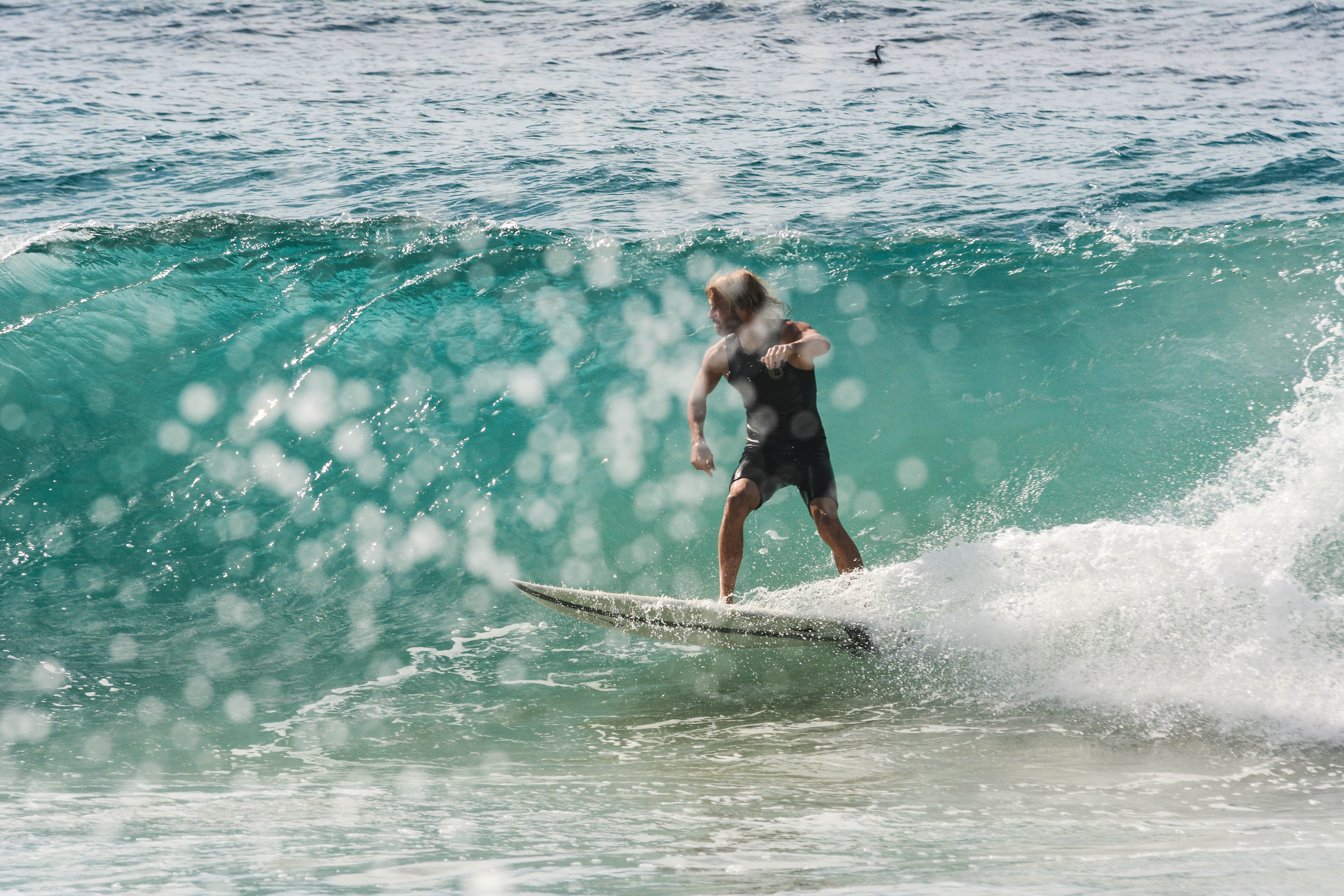 Person Surfing on Body of Water