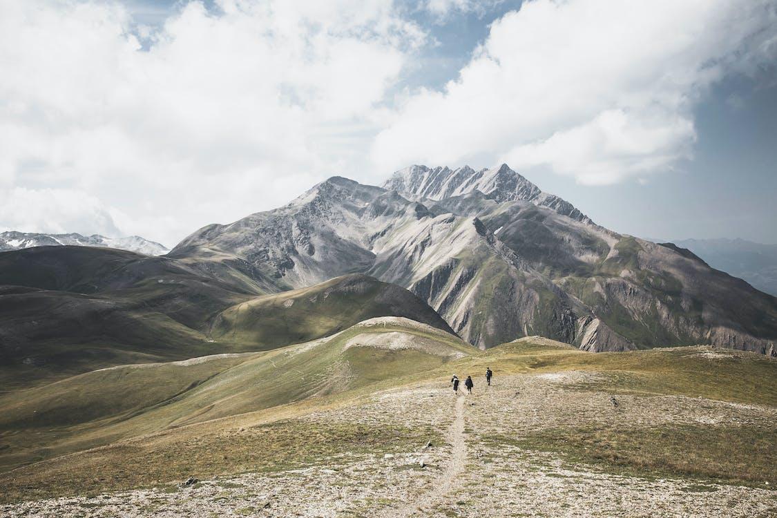 白い曇り空の写真の下で緑と茶色の山