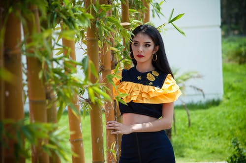 Woman Wearing Black And Yellow Crop Top Holding Bamboo