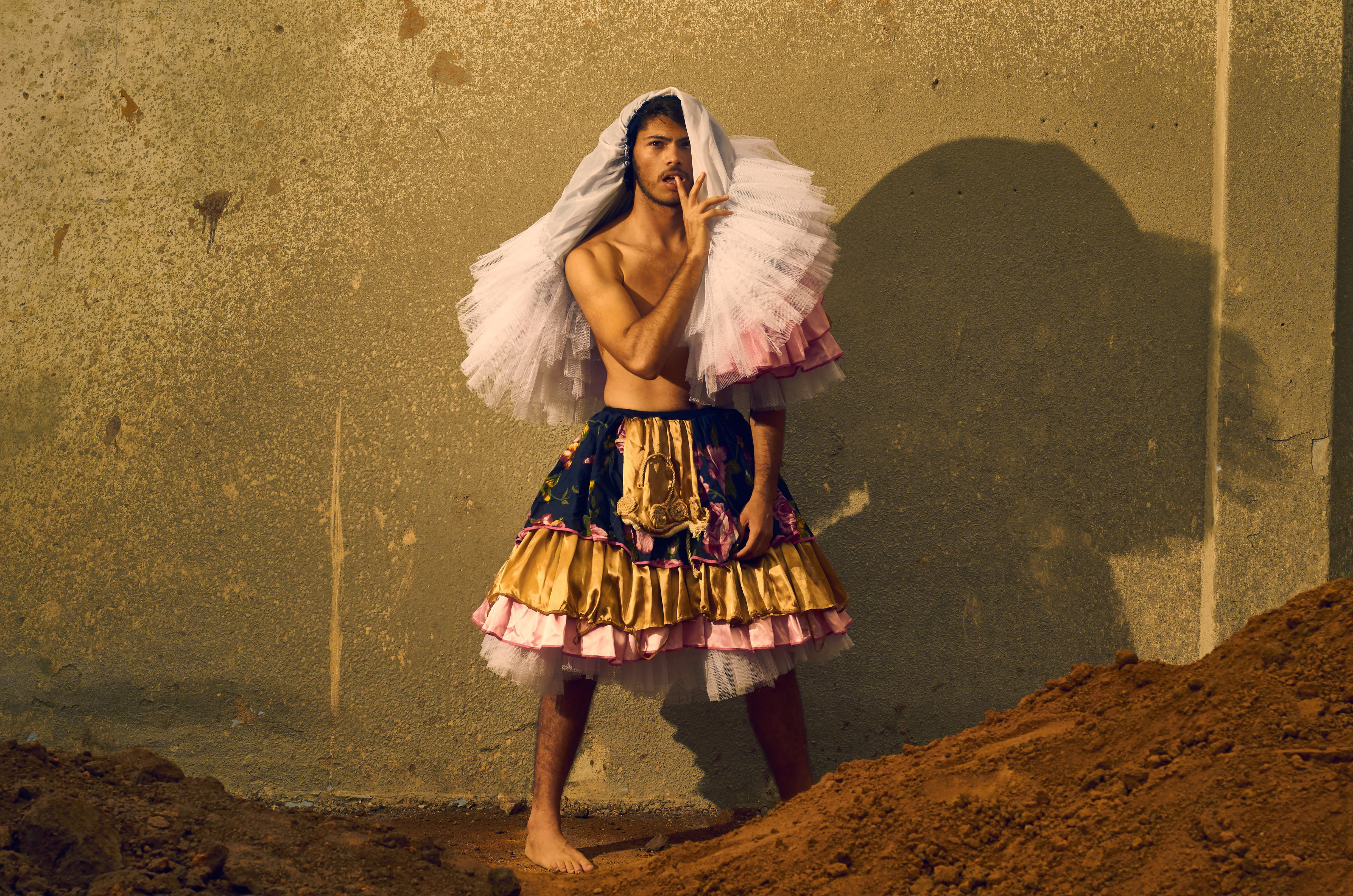 Man Wearing Gold and Pink Skirt
