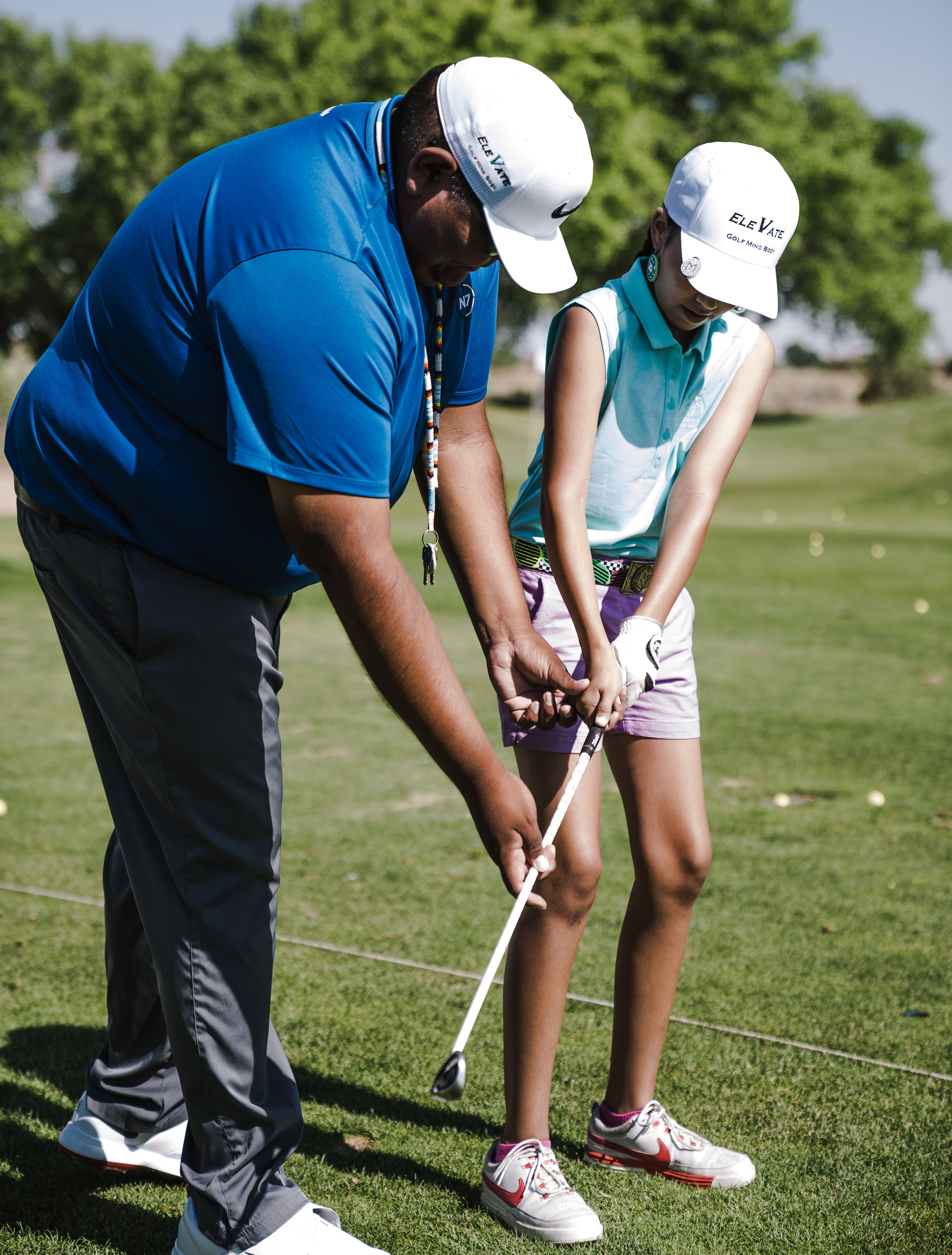 Man Teaching Girl How to Putt