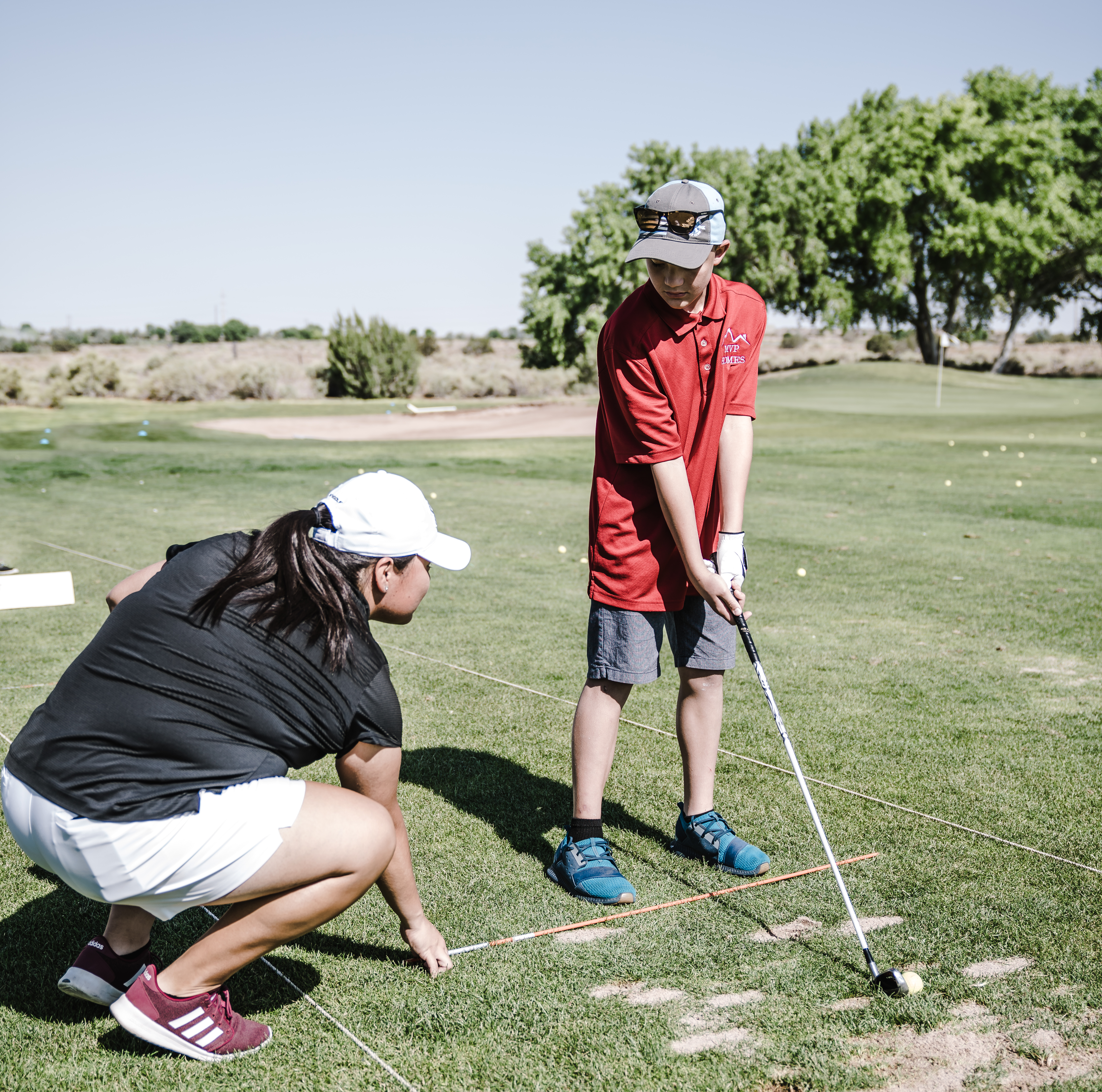 Boy Holding Golf Club in Front of Crouching Woman