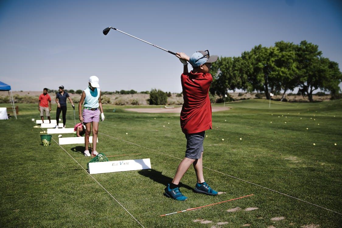 Person Swinging Golf Club on Field