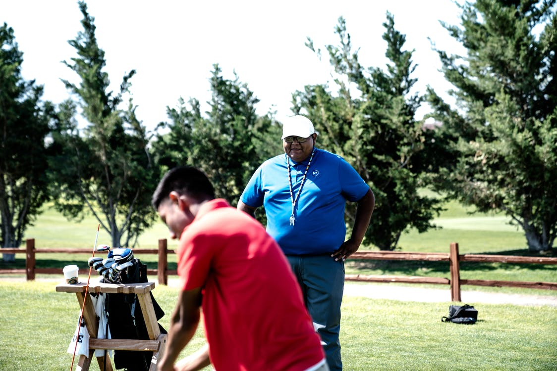Man in Red Polo Shirt Standing Near Man in Blue Top Holding His Waist