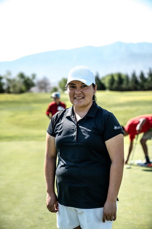Smiling Woman Standing on Golf Course