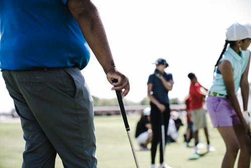 Person Holding Golf Club Near Girl and Woman