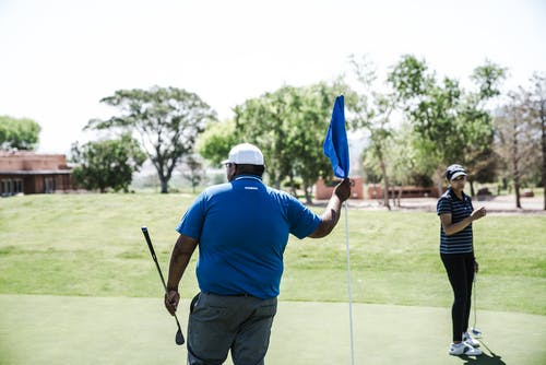 Person Holding Blue Flaglet Holding Golf Driver