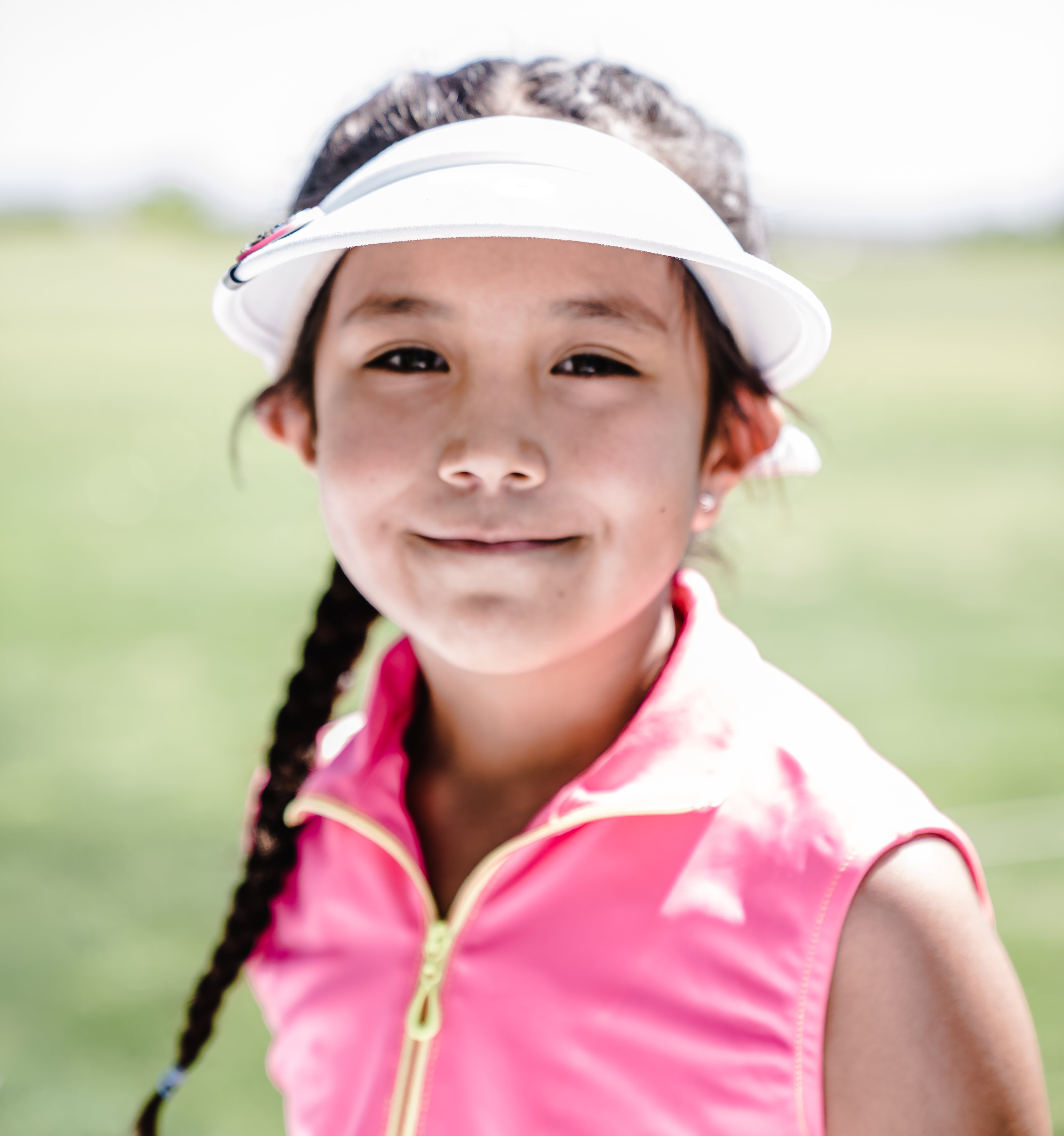 Girl Wearing White Visor Hat And Pink Zip-up Vest