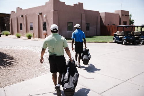Two Men Holding Golf Bags