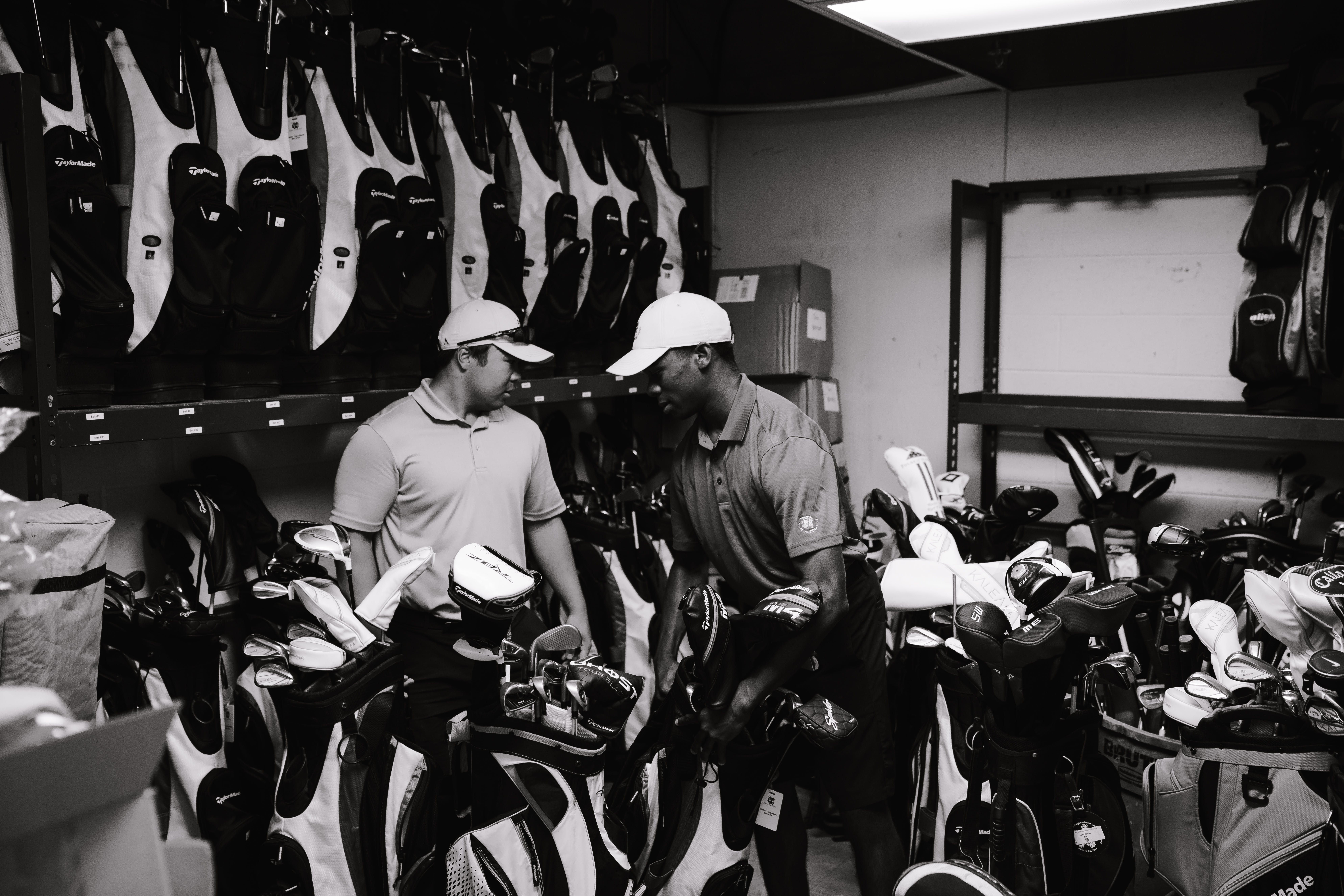 Grayscale Photography Of Men Surrounded By Golf Clubs