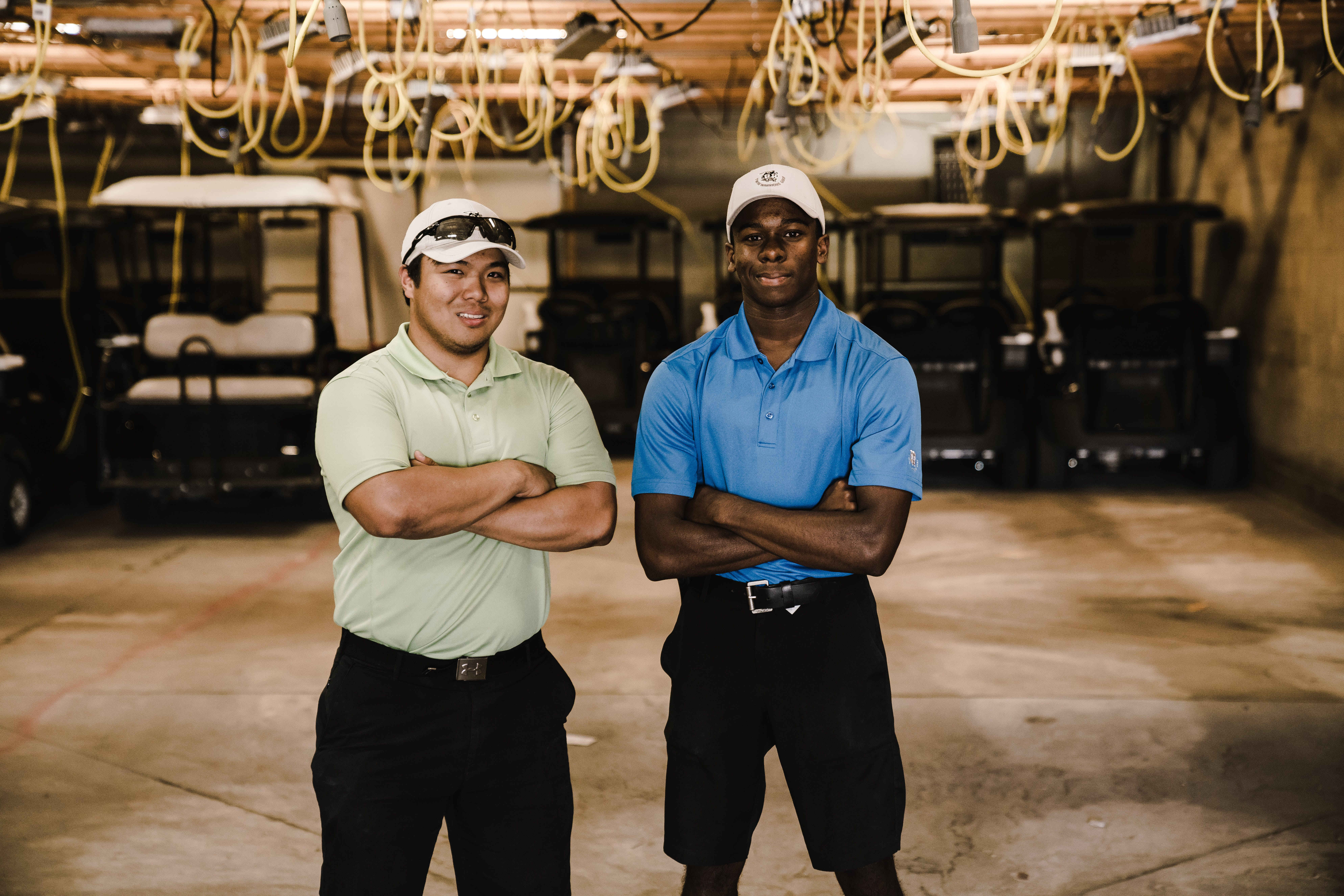Two Men Crossing Arms While Standing Near Golf Carts