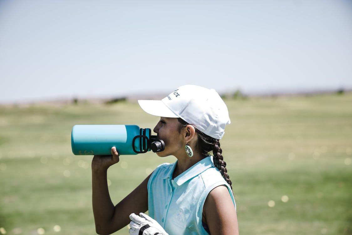 青いスポーツボトルの屋外で飲む女性