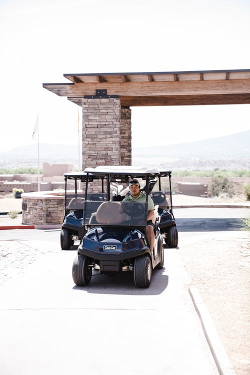 Man Wearing Grey Polo Shirt Riding Blue and White Golf Cart