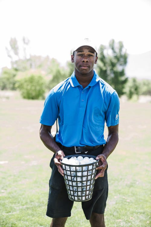 Man Holding Basket of Golf Balls
