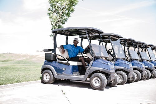 Man in Blue Shirt and Black Shorts Outfit Riding on Blue Golf Cart