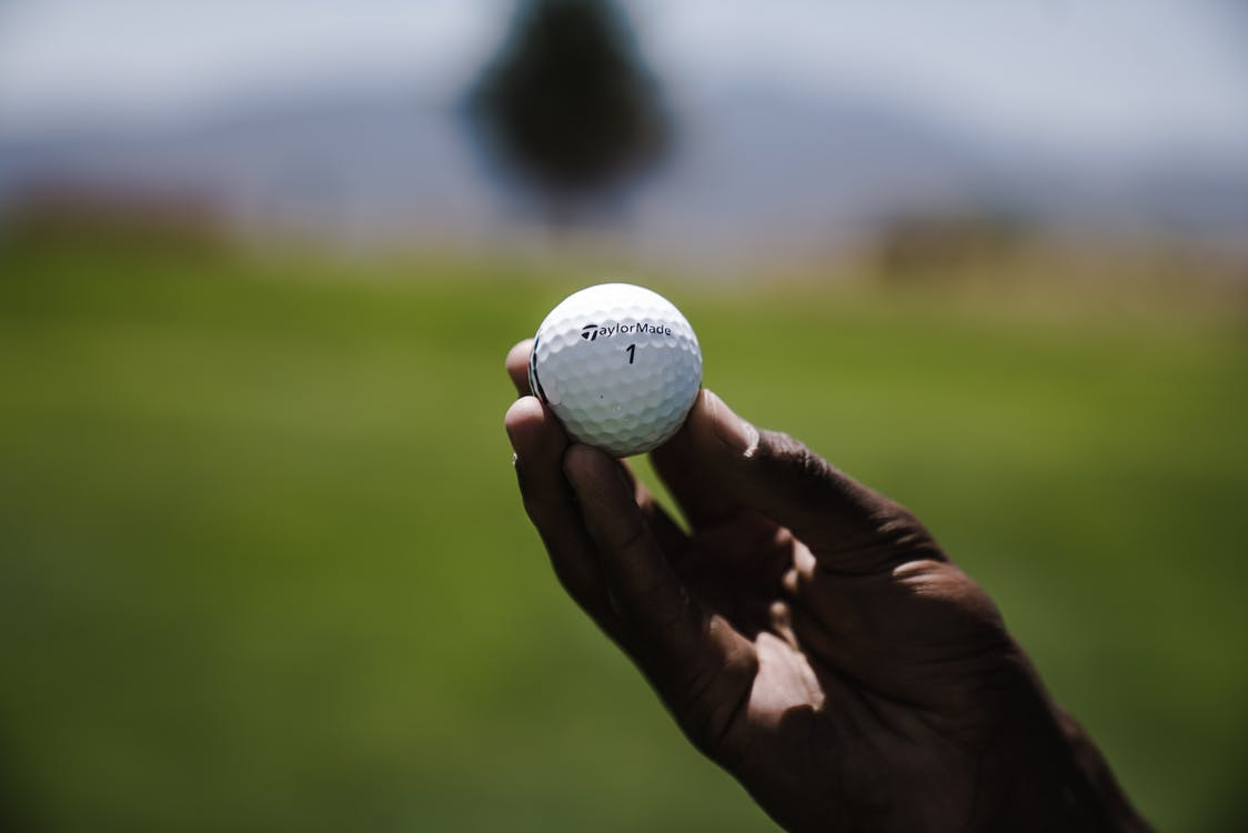 Selective Focus Photography of Person Holding Golf Ball