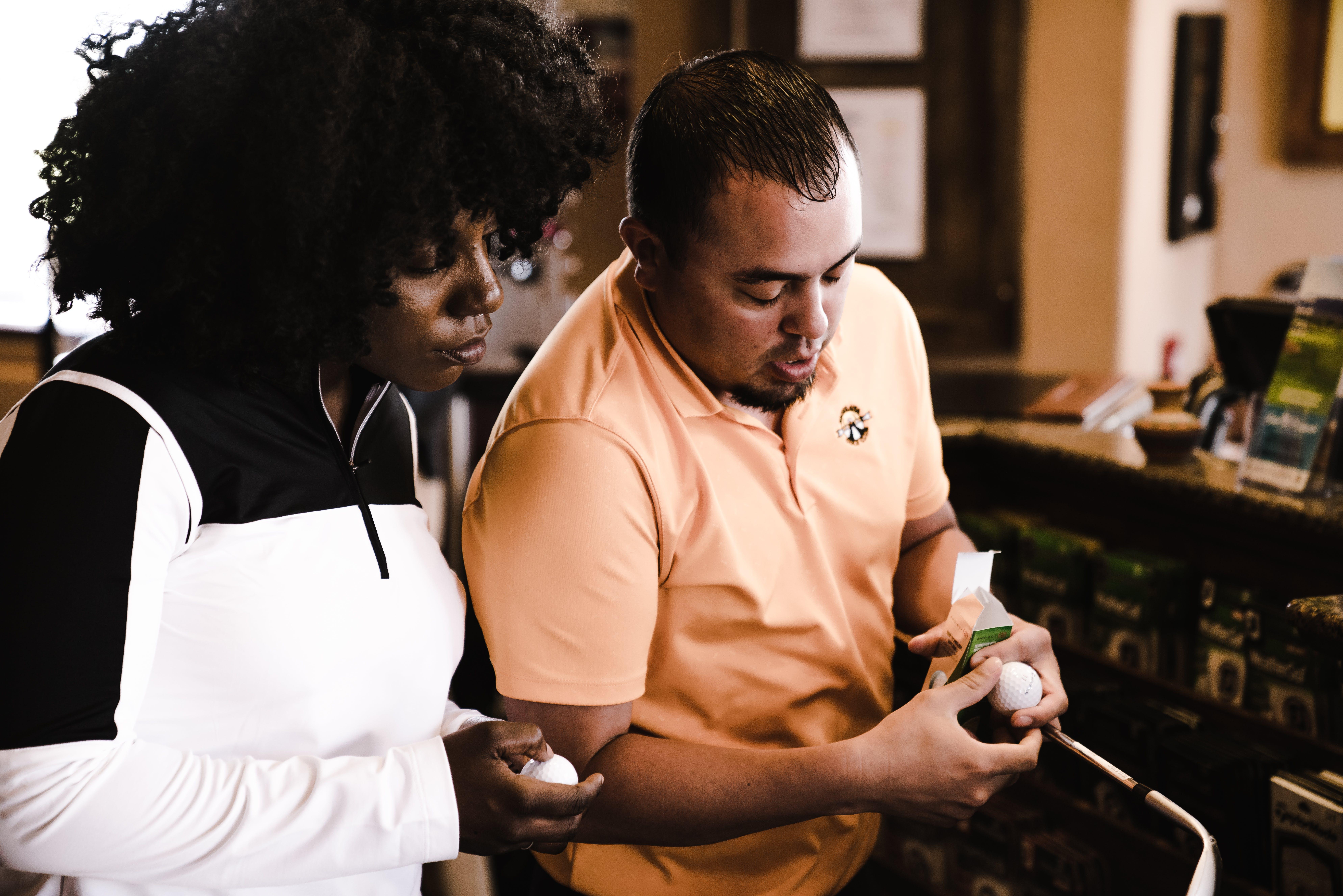 Woman and Man Looking at Golf Balls