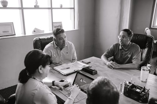 Grayscale Photo of People Inside A Room Having A Meeting