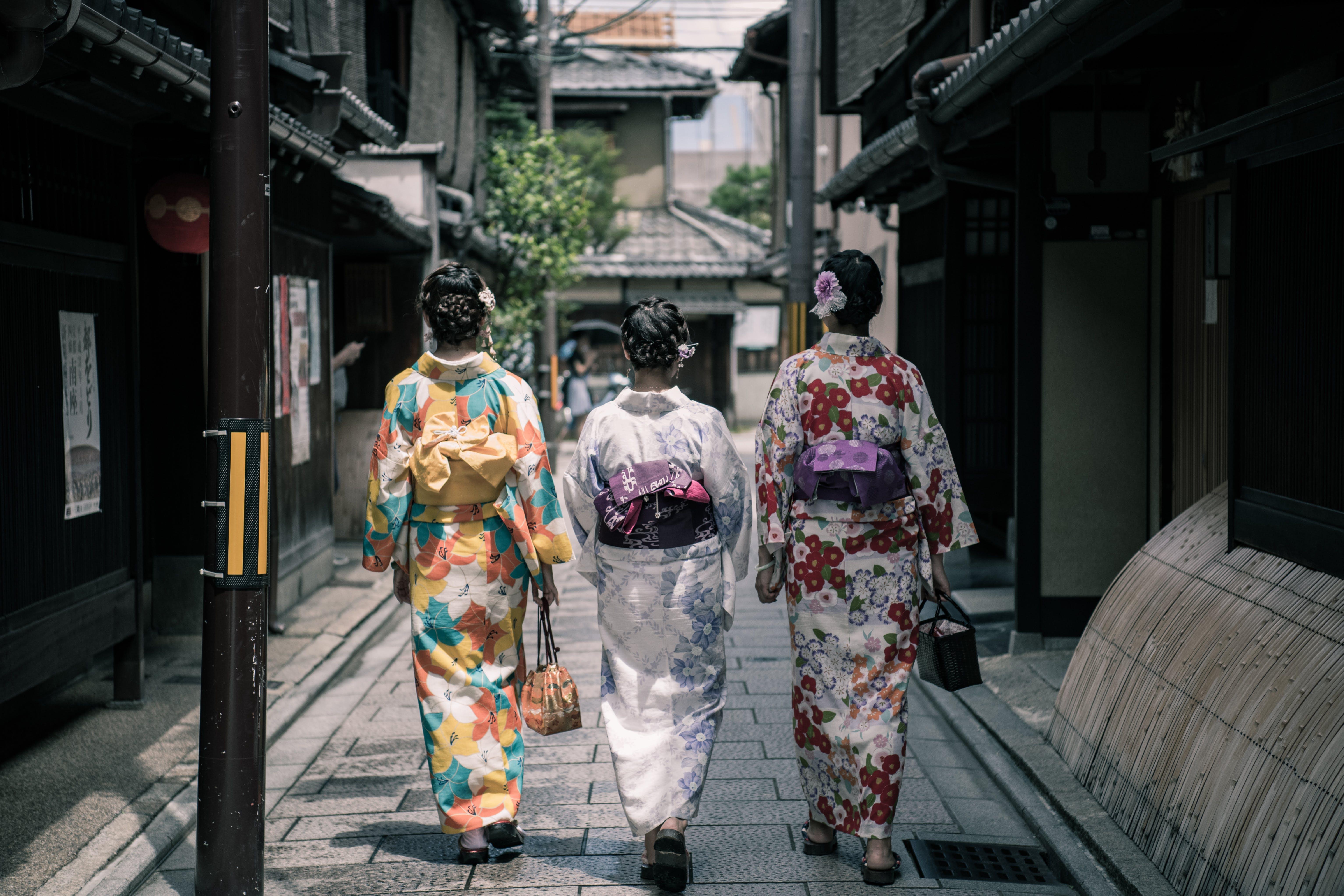 Three Geisha Walking Between Buildings