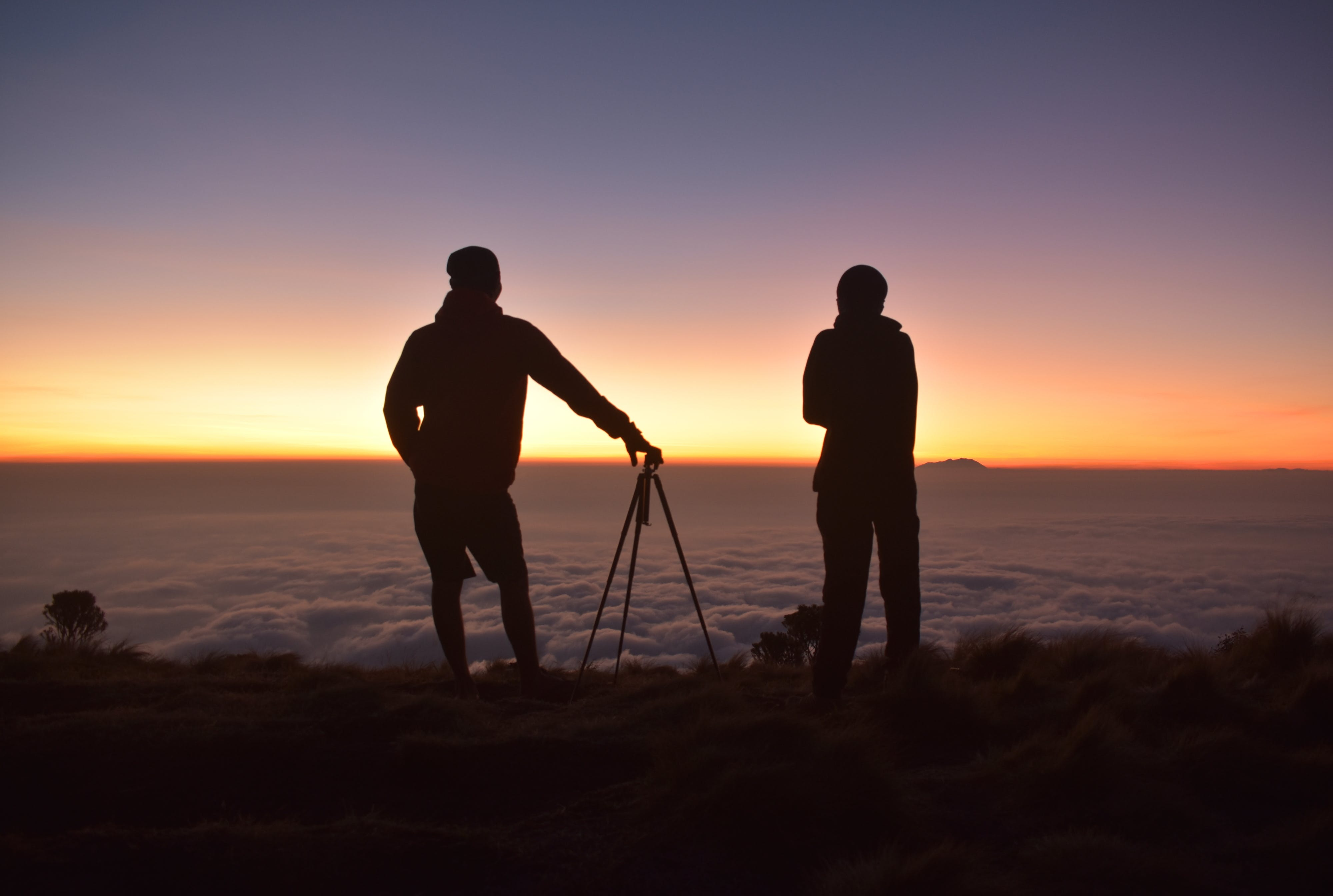 Silhouette of People on Mountain Tops Looking on Sea of Clouds