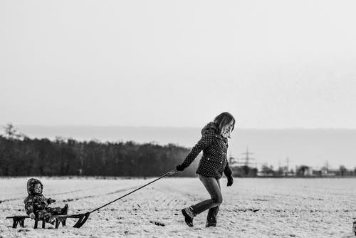 Woman Pulling Snow Sled With Baby